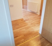 Top layer oak real wood flooring with low thresholds at doors giving the customer wheelchair accessibility