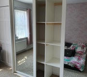 White framed sliding mirror doors with white internal shelving to centre with single hanging to one side and double hanging to other